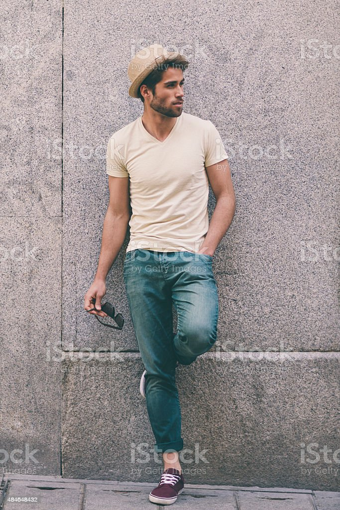 Young guy standing against a wall stock photo