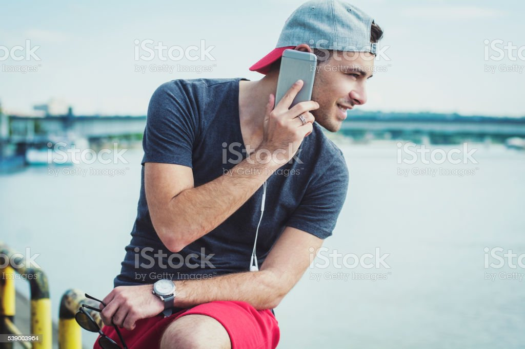 Young guy talking on cell phone next to the river stock photo