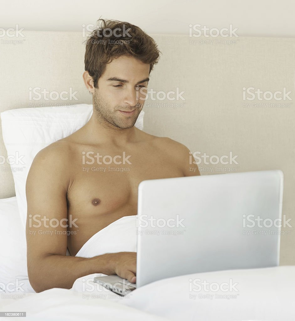 Young guy using a laptop while sitting in bed royalty-free stock photo