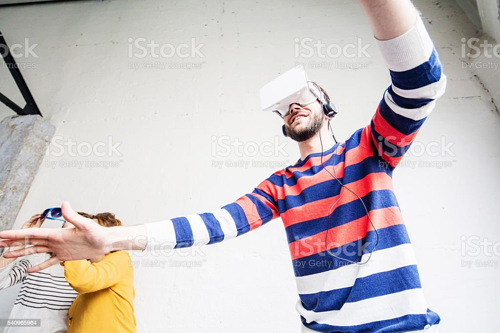 Young guy wearing virtual reality goggles and headphones stock photo