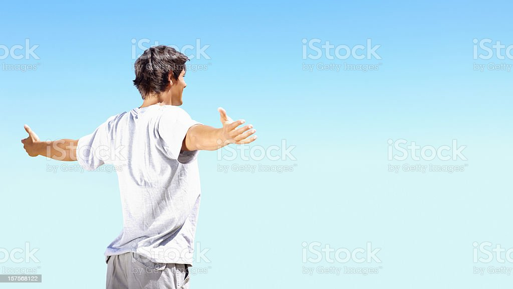 Young guy with arms outstretched against blue sky royalty-free stock photo