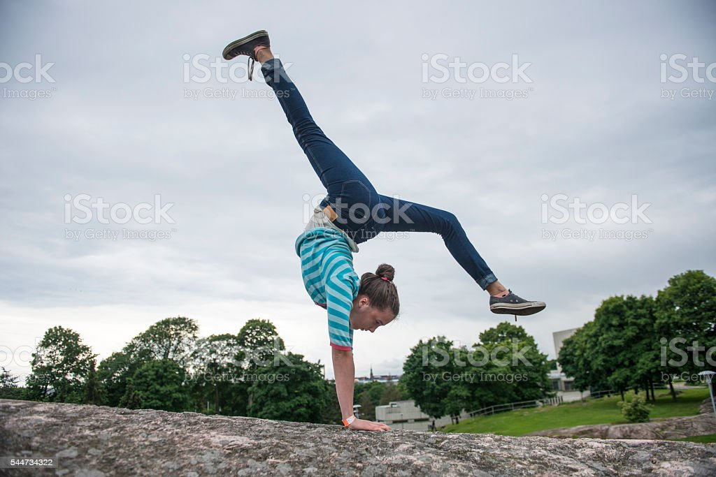Young gymnast balancing in park. stock photo