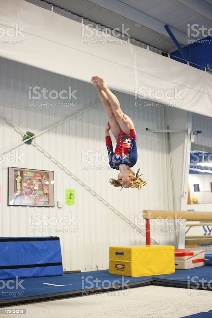 Young Gymnast Doing Backflip on Trampoline stock photo