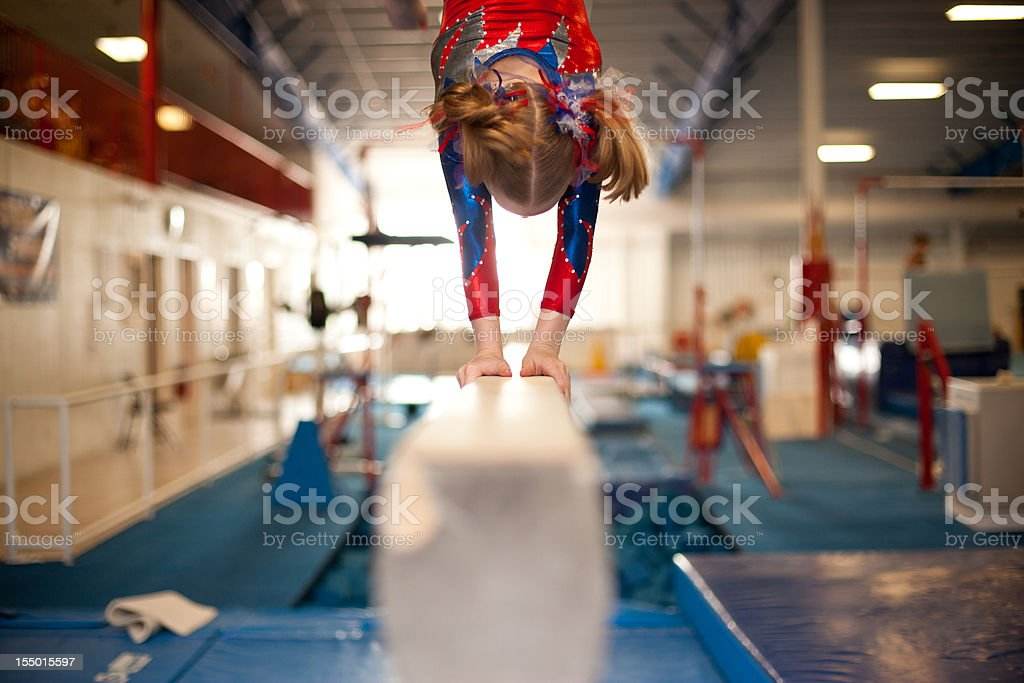 Young Gymnast Doing Handstand on Balance Beam stock photo