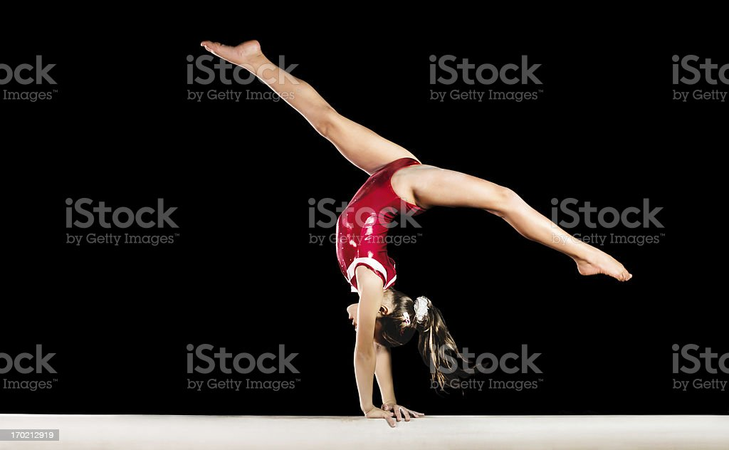 Young gymnast girl exercising on balance beam. stock photo