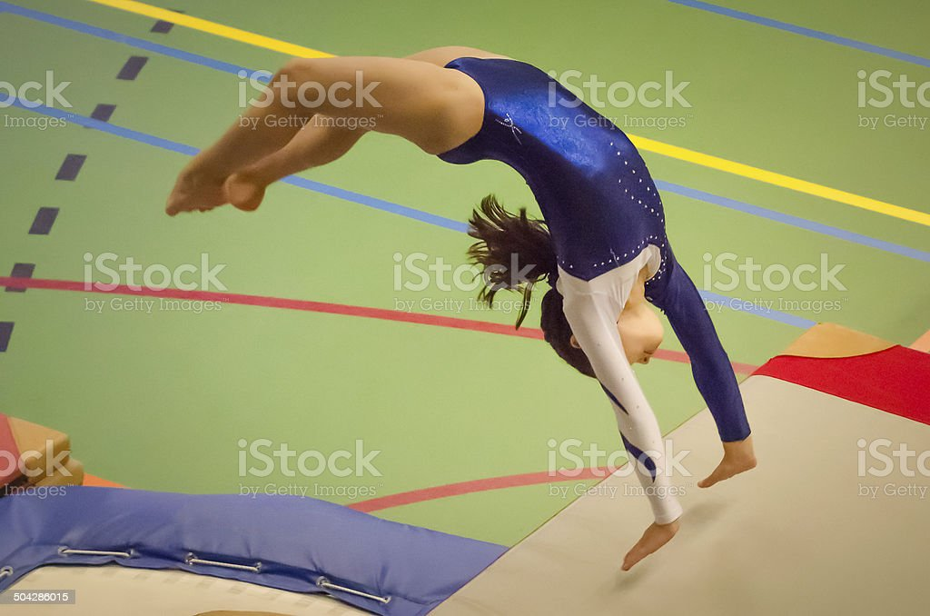 Young gymnast girl performing jump back handspring stock photo
