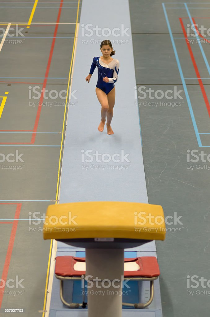 Young gymnast girl performing jump stock photo
