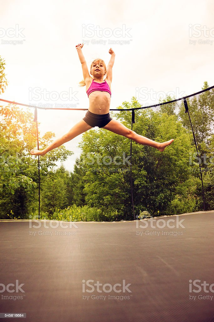Young gymnast on a backyard trampoline in summer. She is around 9...