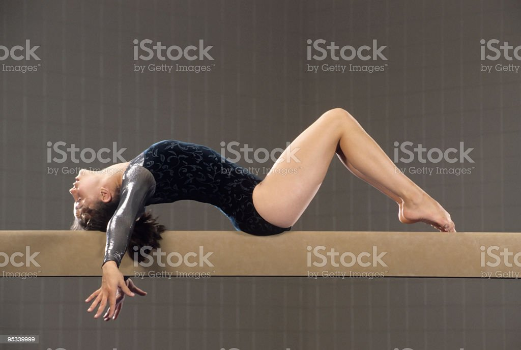 Young gymnast performing on the balance beam stock photo