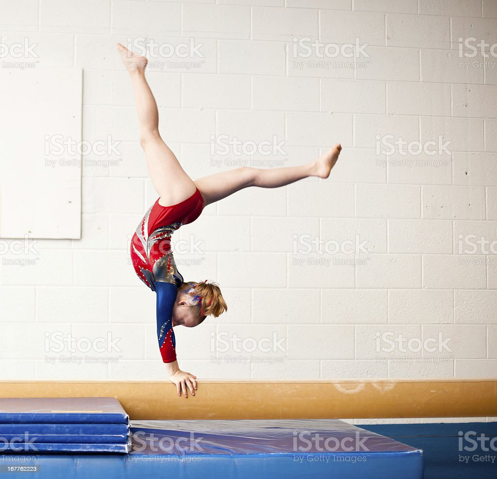Young Gymnast Performing Walkover on Balance Beam stock photo