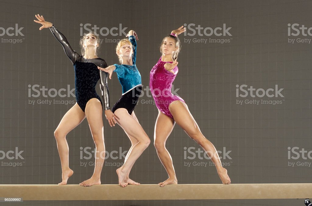 Young gymnasts performing on balance beam stock photo