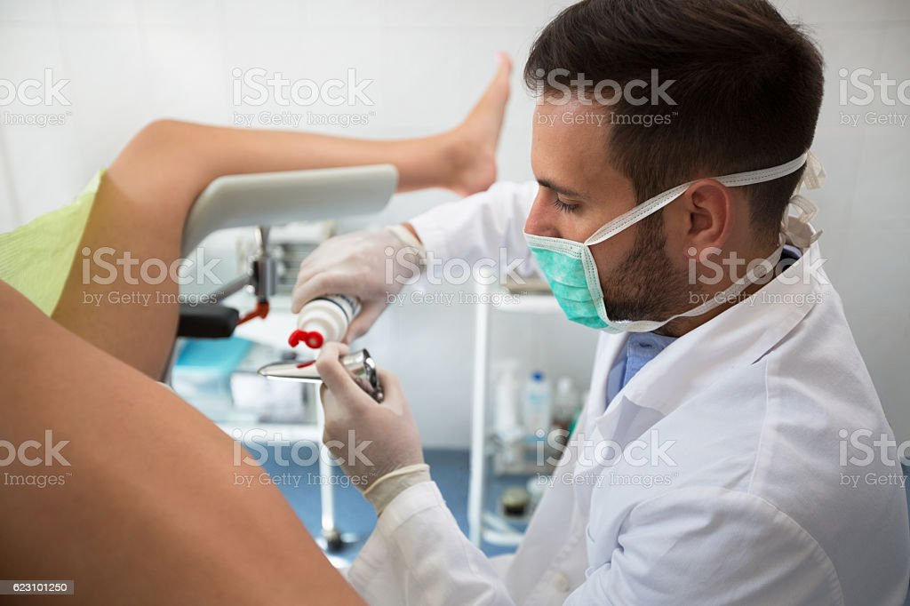 Young  gynecologist putting gel on equipment to exam patient stock photo