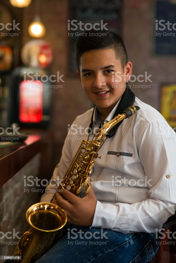 Young gypsy saxophone player. stock photo