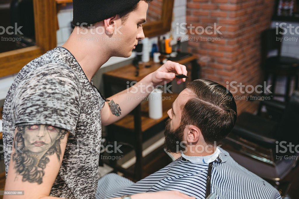 Young hairstylist combing hair of male client with comb stock photo
