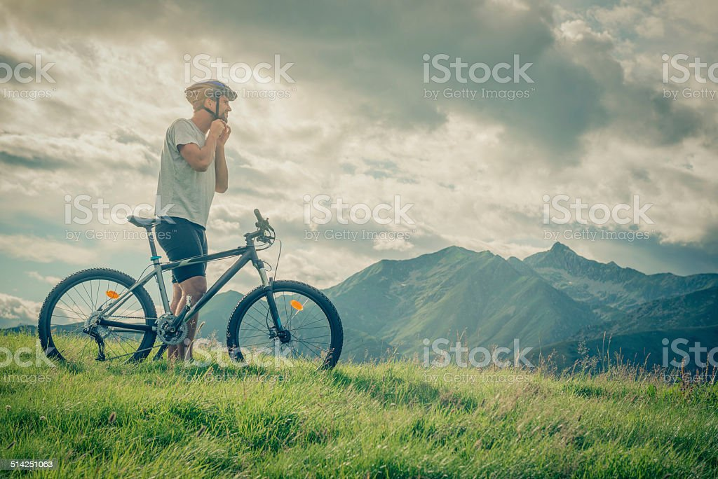 Young half-face man wear helmet near bike on mountain outdoor stock photo