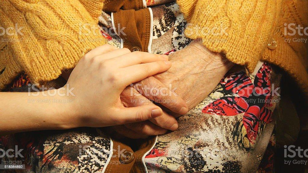 Joven de la mano de una antigua reconfortante par de manos foto de stock libre de derechos