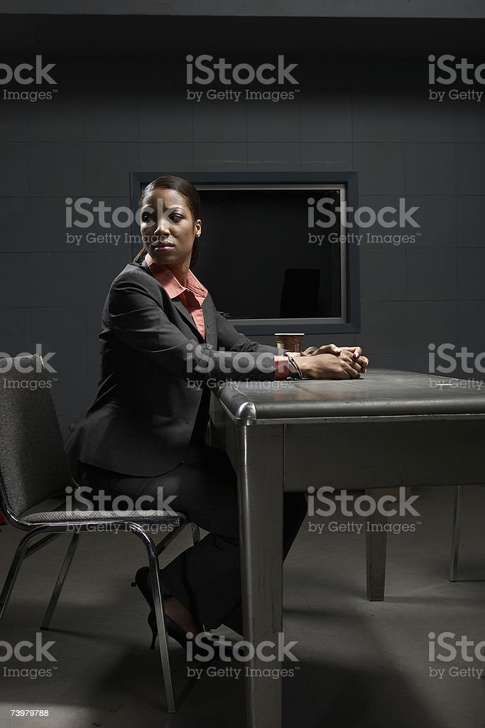 Young handcuffed woman sitting at desk in interrogation room, looking away stock photo