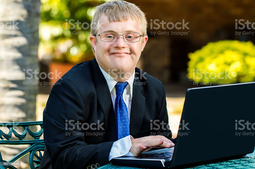 Young handicapped businessman working with laptop. stock photo