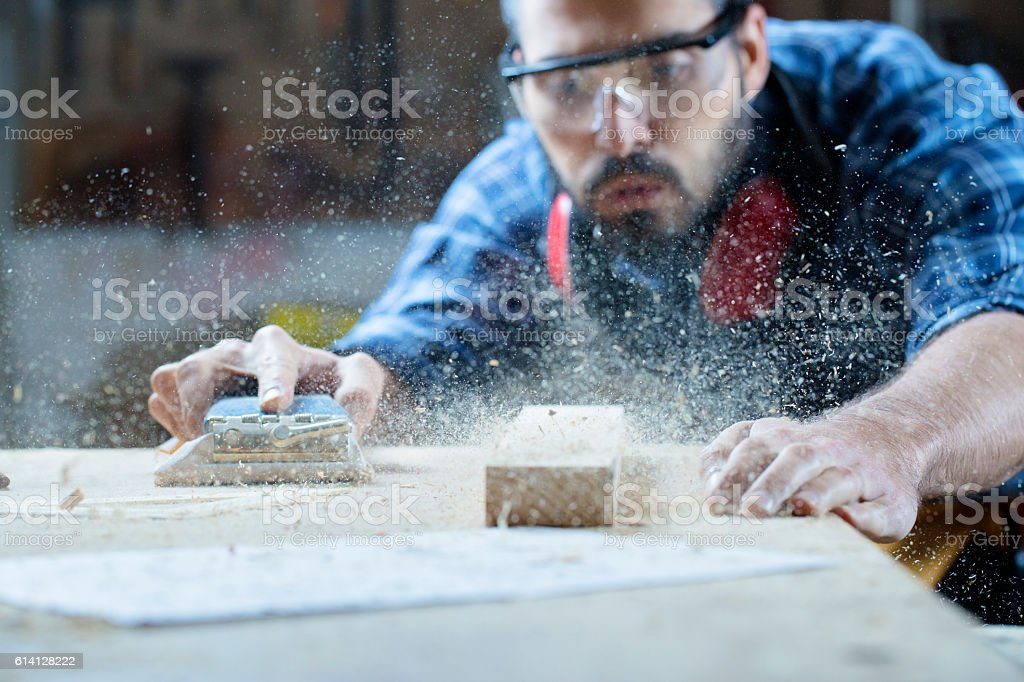 Young handosme carpenter blowing off sawdust stock photo