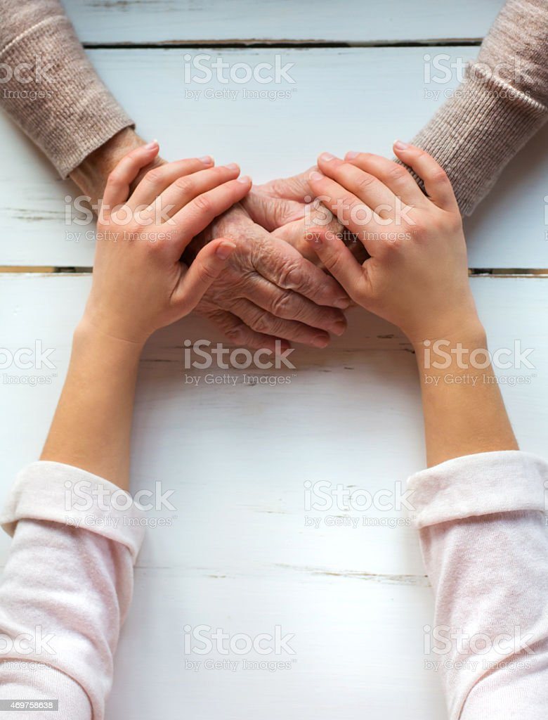 Young hands on those of a senior woman on a wooden table stock photo