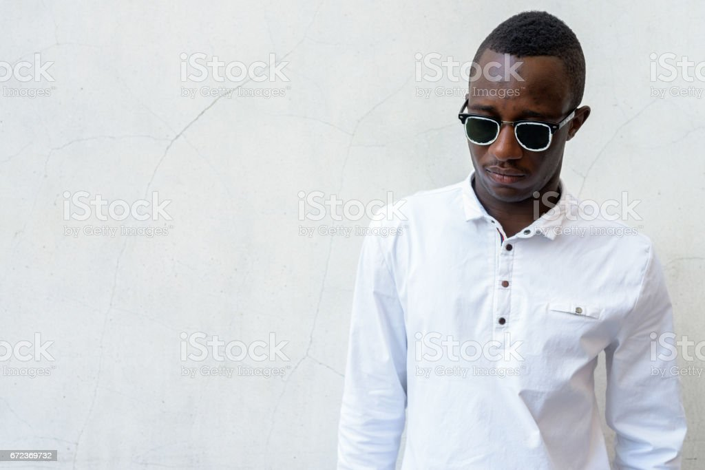 Young handsome African man against gray concrete wall stock photo