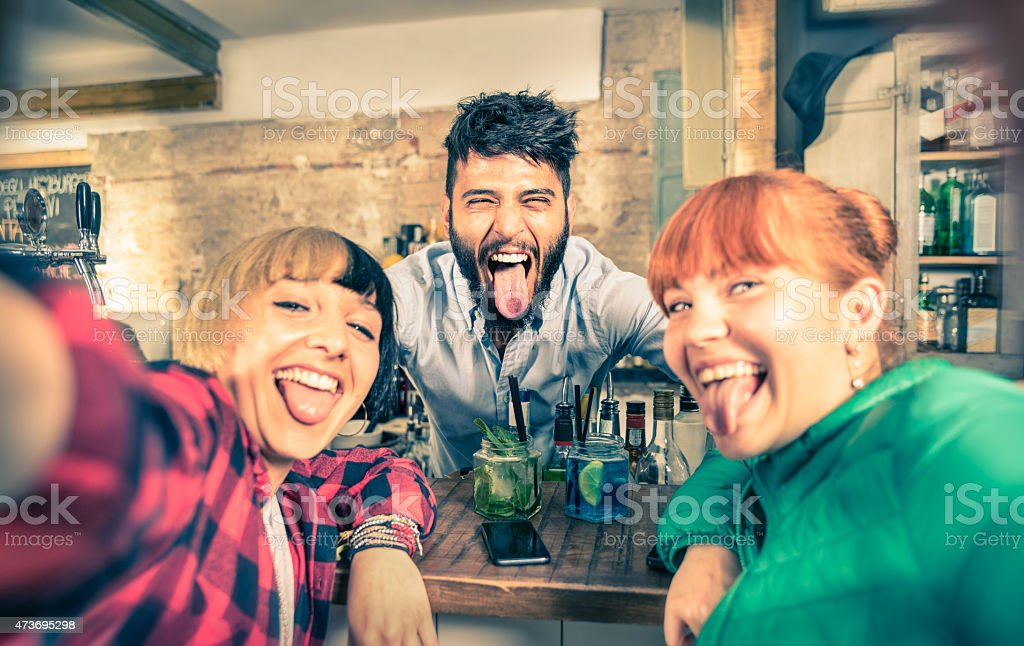 Young handsome bartender flirting with beautiful girls at cocktail bar stock photo
