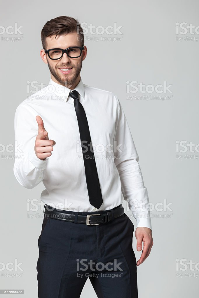 Young handsome businessman pointing at you - isolated on gray. stock photo