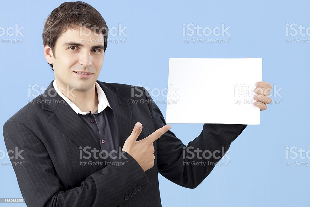 Young handsome businessman showing a blank paper. royalty-free stock photo