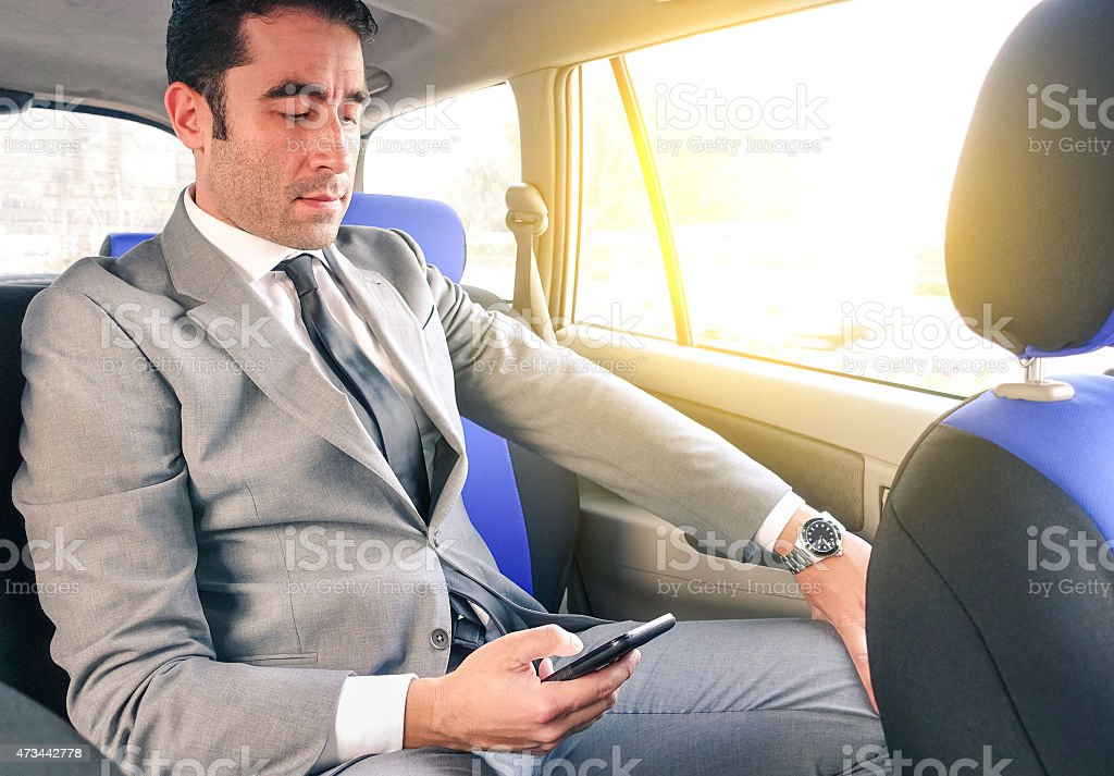 Young handsome businessman sitting in taxi cab while texting sms stock photo