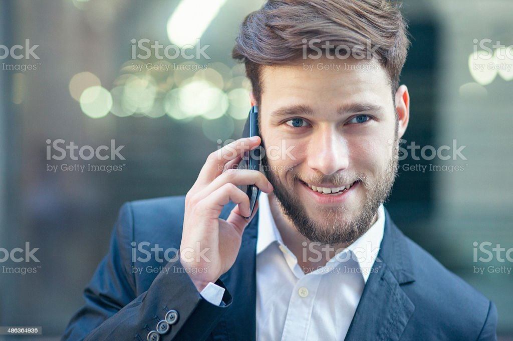 Young handsome businessman taling on the smart phone stock photo