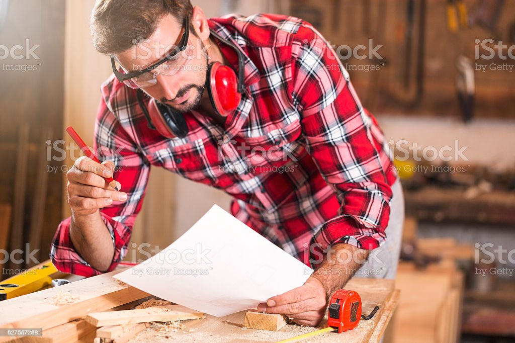 Young handsome carpenter drawing sketches royalty-free stock photo
