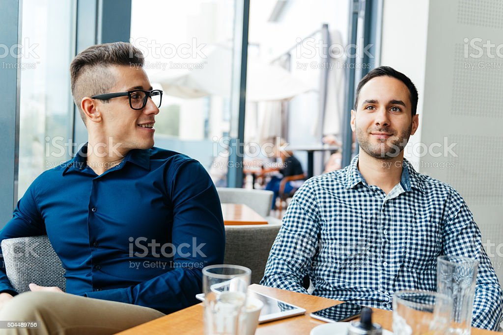 Young handsome casual men drinking coffee and discuss in cafe stock photo