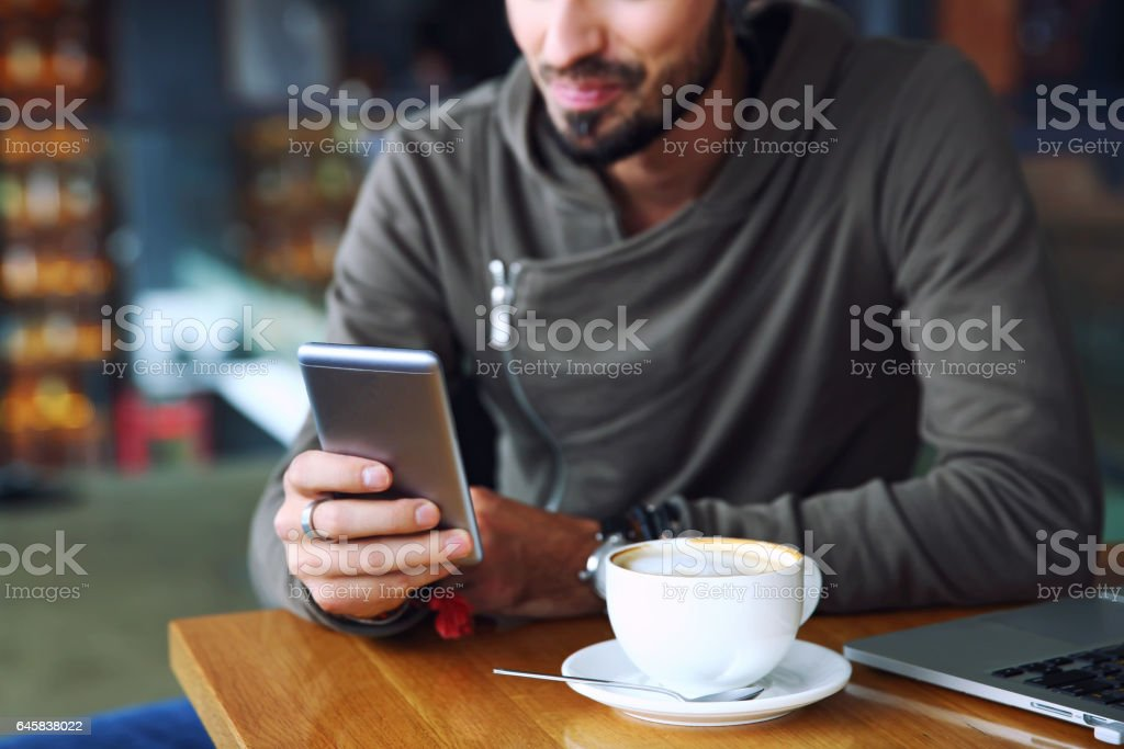Young handsome cheerful hipster guy at the restaurant using a mobile phone, hands close up. Selective focus stock photo