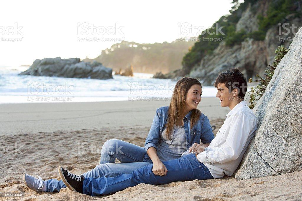 Jeune beau couple assis sur la plage. photo libre de droits