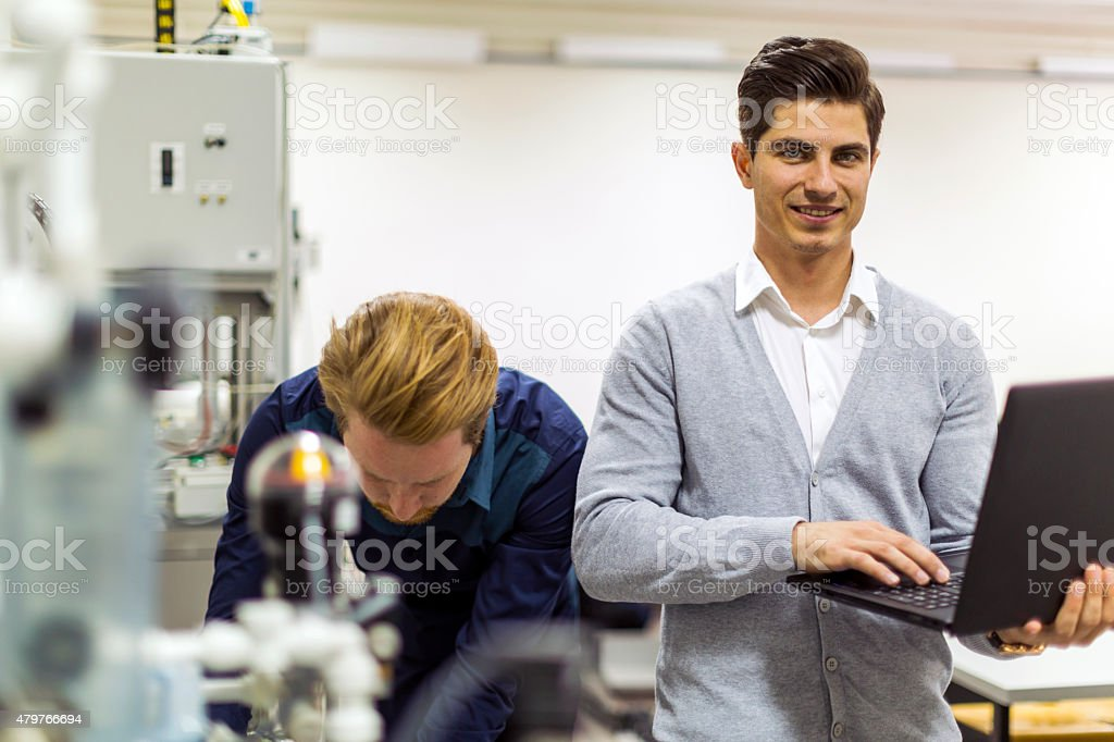 Young handsome engineer checking data on a laptop stock photo
