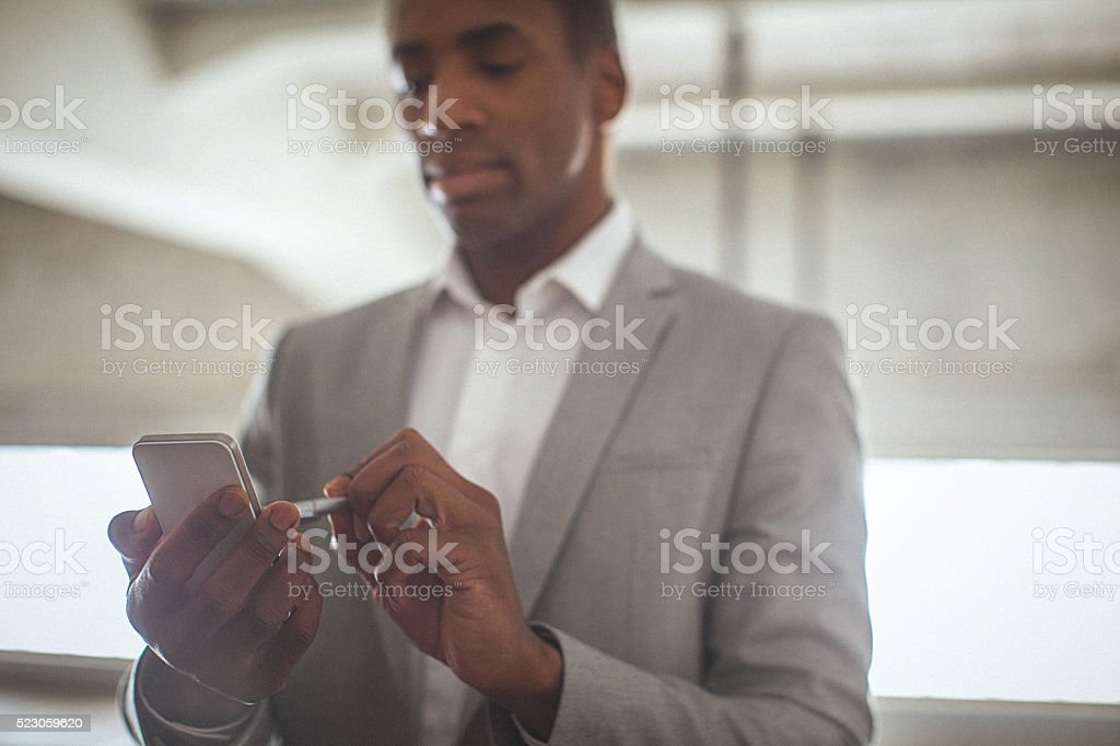 Young handsome entrepreneur typing text message on his smartphon stock photo