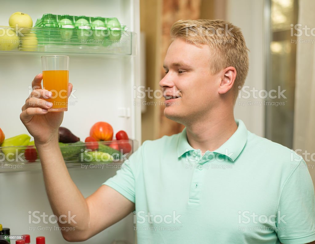 Young handsome happy man smiling, holding a glass of juice stock photo