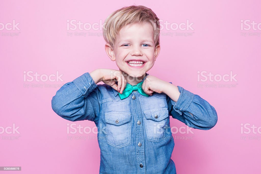 Young handsome kid smiling with blue shirt and butterfly tie stock photo