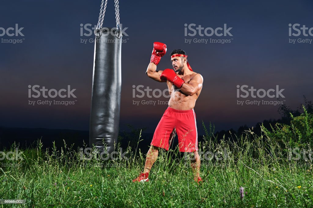 Young handsome male boxer practicing on a punching bag outdoors stock photo