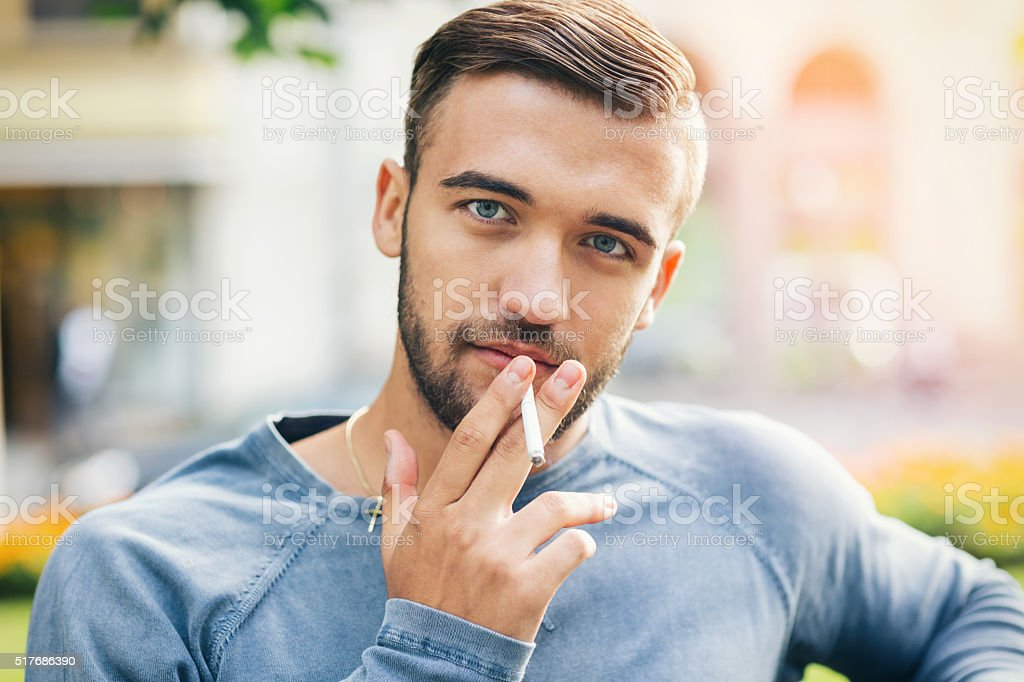 Young handsome male smoking stock photo