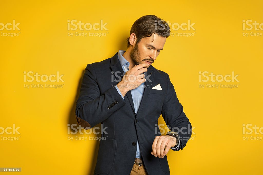 Young handsome man checking the time stock photo