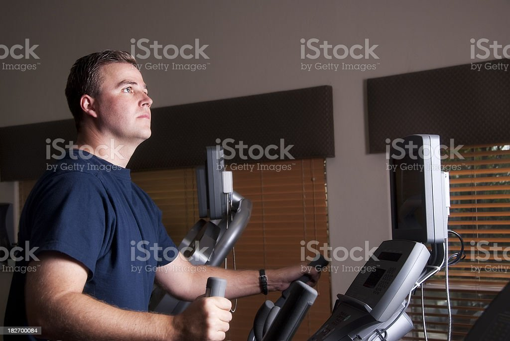 Young handsome man exercising on the elliptical machine royalty-free stock photo