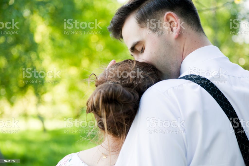 Young handsome man gently kissing his fiancee. Love stock photo