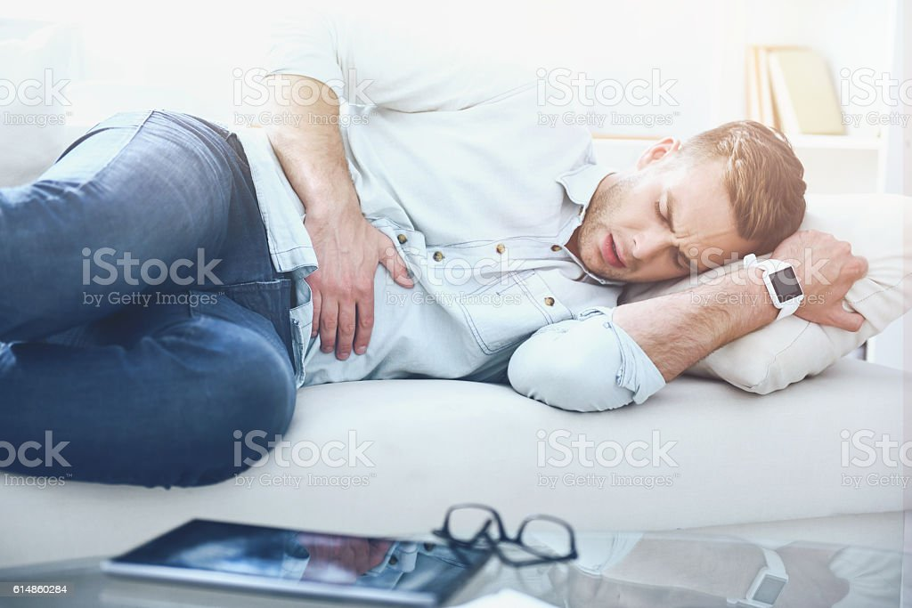 Young handsome man having stomach ache. stock photo