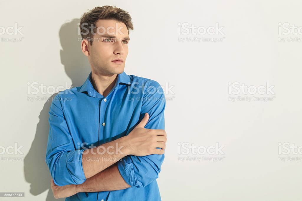 young handsome man holding his hands crossed. stock photo