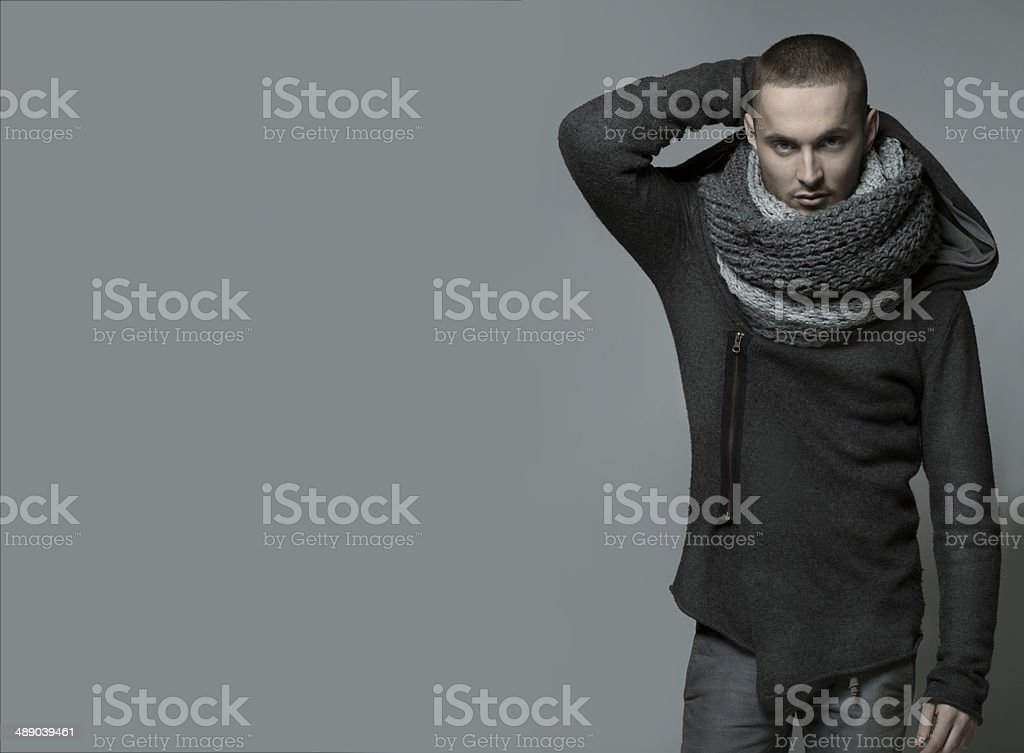 Young handsome man in a grey wrap, shawl stock photo