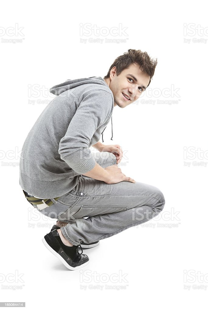 young handsome man in grey blouse crouching stock photo