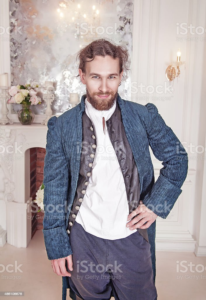Young handsome man in medieval clothes standing stock photo