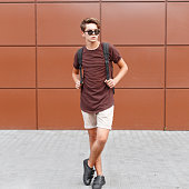 Young handsome man in summer clothes posing near wall