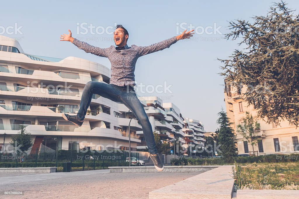 Young handsome man jumping in the city streets stock photo